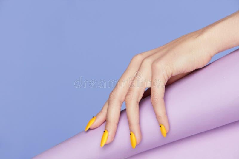 钉子设计 有明亮的黄色修指甲的手 免版税库存照片