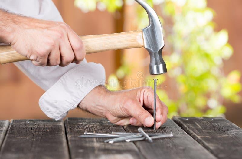 钉牢钉子的木匠 图库摄影
