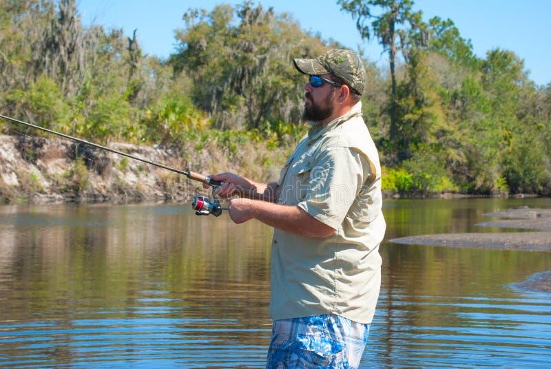钓鱼一条小河的渔夫 图库摄影
