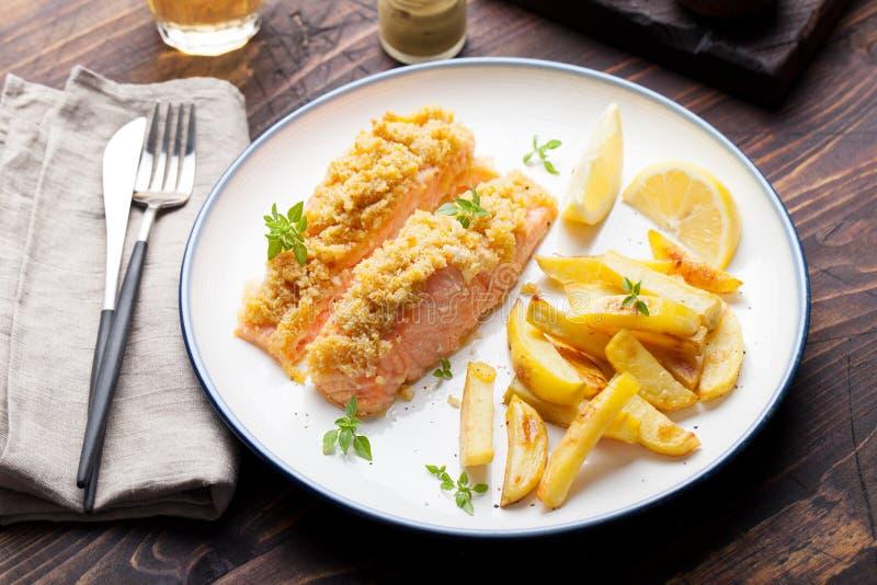 钓鱼三文鱼与弄皱在上面用被烘烤的土豆和柠檬切片 免版税库存照片