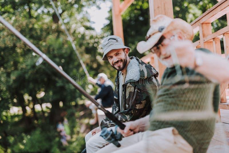 钓鱼与他年迈的父亲的正面有胡子的人 免版税库存图片