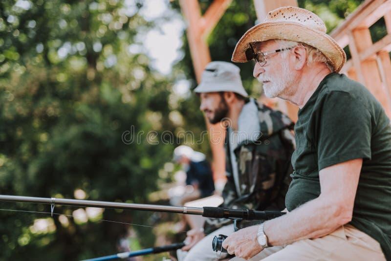 钓鱼与他的儿子一起的宜人的年长人 库存图片