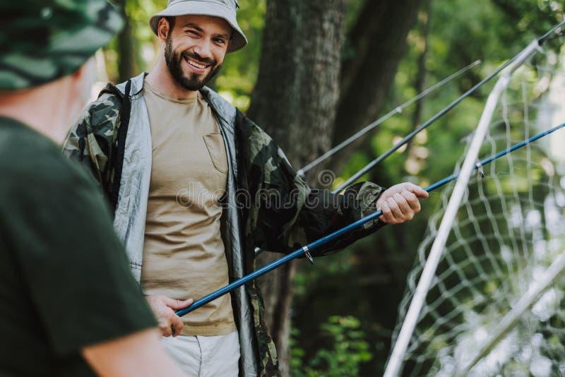 钓鱼与他的父亲的正面微笑的人 免版税库存图片