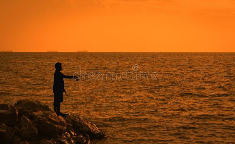钓鱼与在海的实心挑料铁杆的Fisher人 钓鱼在水库的年轻人在日落 库存照片