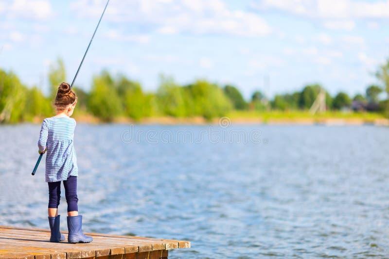 钓鱼从在湖的木码头的胶靴的逗人喜爱的小孩女孩 在夏天好日子期间,家庭娱乐活动 免版税库存图片