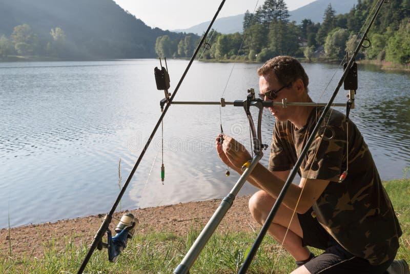 钓鱼冒险,鲤鱼钓鱼 钓鱼者准备设备 免版税库存图片