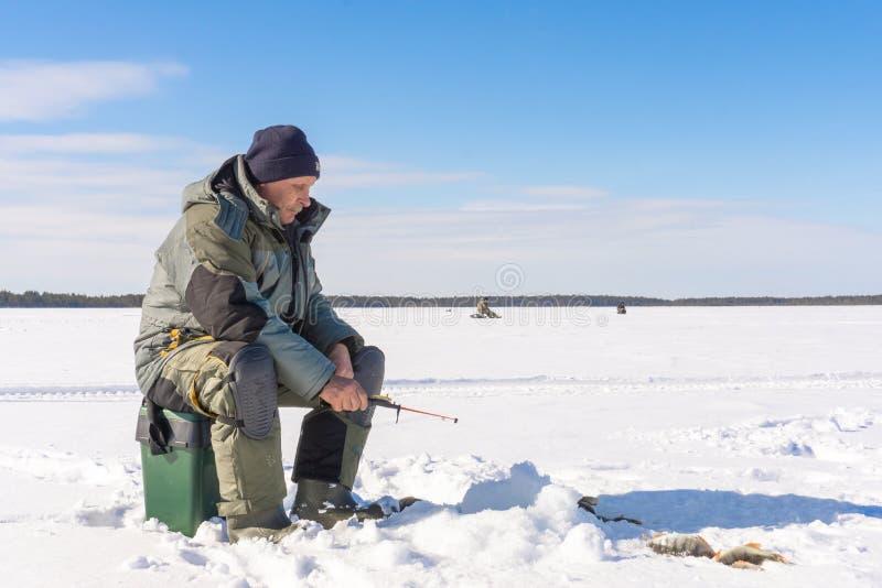 钓鱼冬天钓鱼的渔夫在一明亮的好日子 免版税库存照片