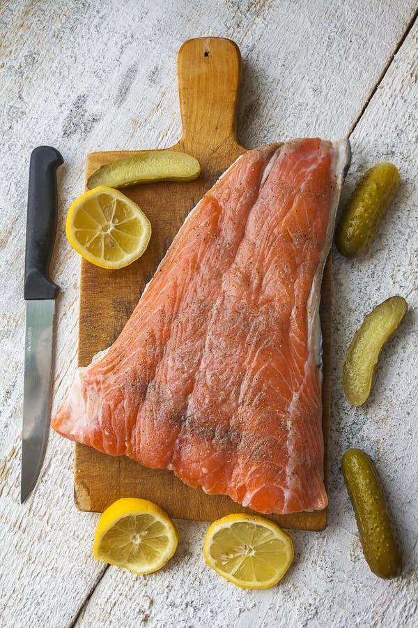 钓鱼吃食物的三文鱼未加工的切片切板 库存图片