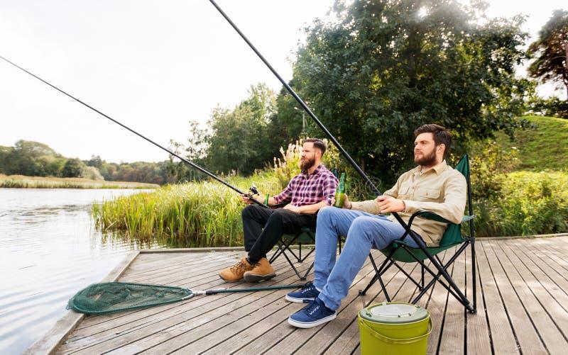 钓鱼和喝在湖的男性朋友啤酒 免版税库存照片