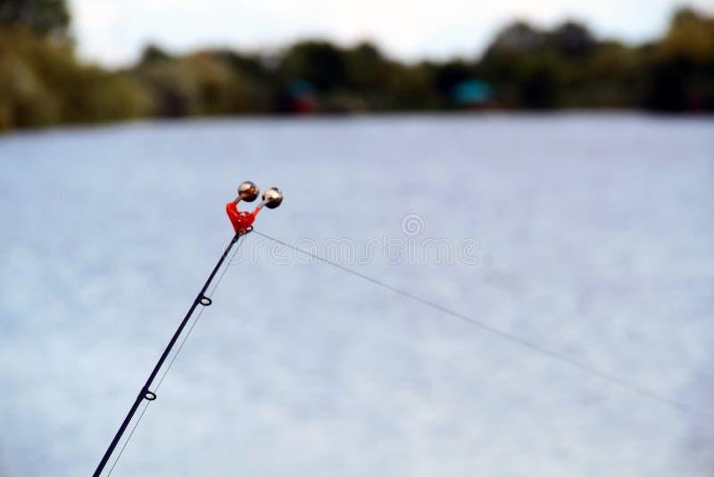 钓鱼响铃在池塘的背景的钓鱼竿结束时 库存图片