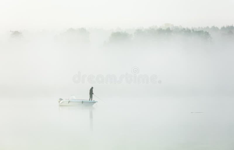 钓鱼在一场厚实的早晨雾 免版税库存照片
