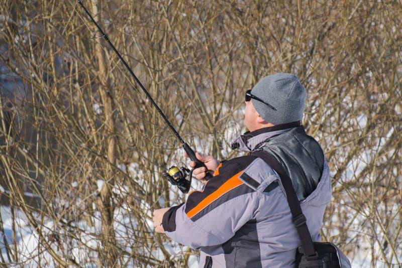 钓鱼在冬天的开阔水域 准备的渔夫扮演锭床工人 图库摄影