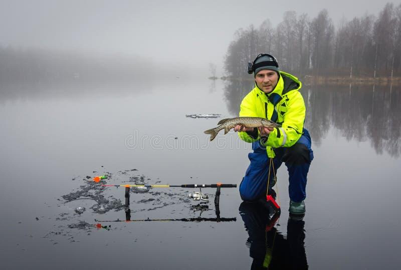 钓鱼在冰的人矛 库存图片