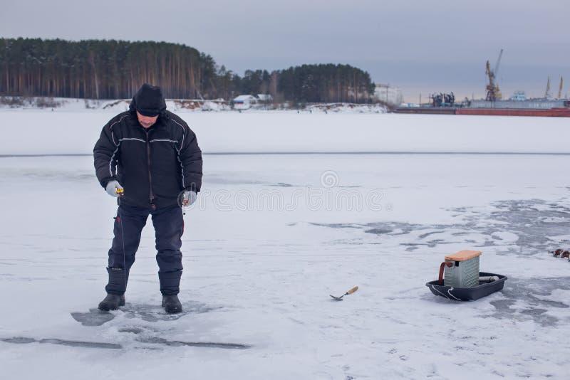 钓鱼在冻河的冬天钓鱼竿的黑暗的衣裳的年长渔夫 库存照片