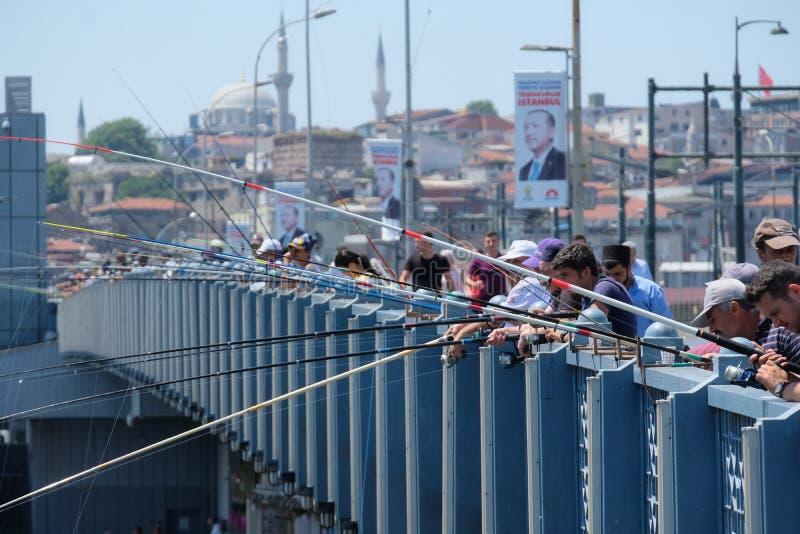 钓鱼在加拉塔桥梁在日落前, Eminonu区,伊斯坦布尔,土耳其的当地居民 库存图片