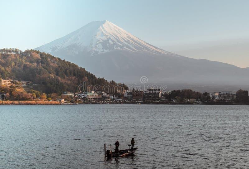 钓鱼在小船的两位渔夫在河口湖和富士山 免版税库存图片