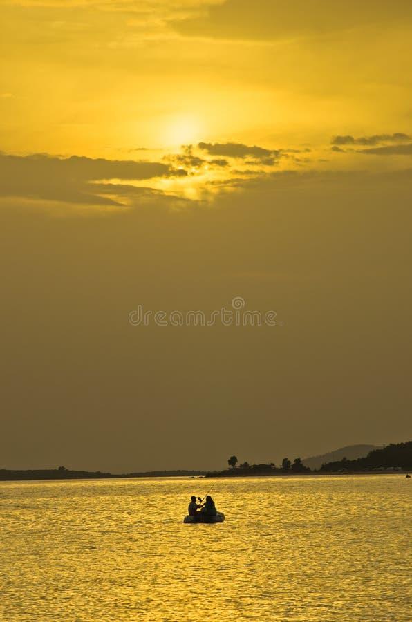 钓鱼在日落在黄灯的射线和反射下, Sithonia 库存照片
