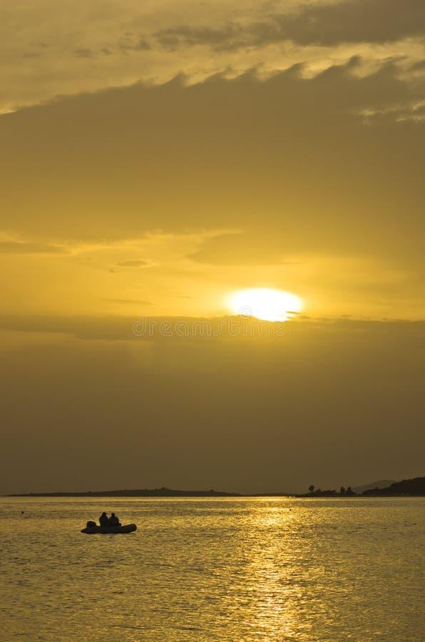 钓鱼在日落在黄灯的射线和反射下, Sithonia 免版税图库摄影