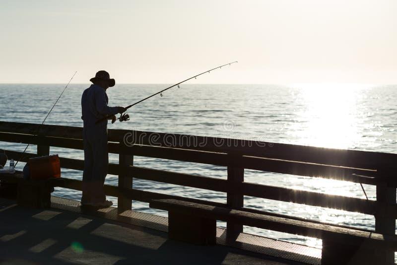 钓鱼在日落的一个码头剪影 库存照片