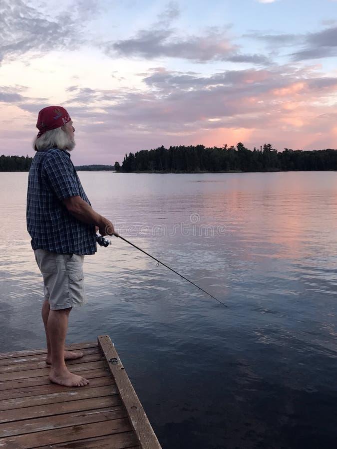 钓鱼在日落,伍兹湖, Kenora,安大略 免版税库存照片