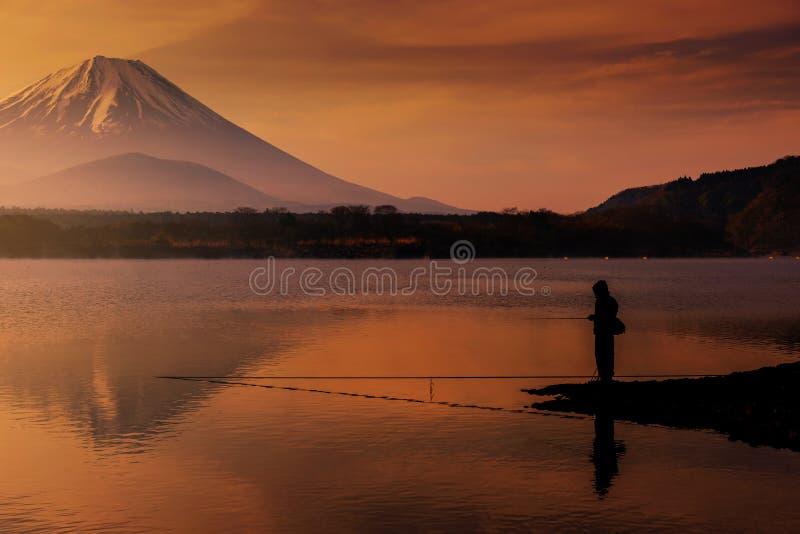 钓鱼在有富士山视图反射的Shoji湖的剪影渔夫在与暮色天空的黎明在山梨 库存照片
