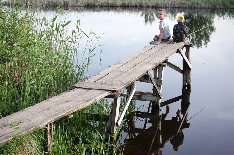 钓鱼在河岸的兄弟 选址用棍子的孩子在手上 库存照片