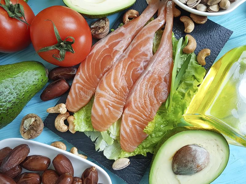 钓鱼在蓝色木背景健康食物的三文鱼沙拉养料Ω 3鲕梨 库存照片