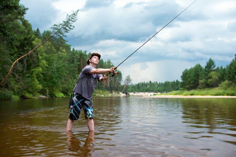钓鱼在风暴前 一个年轻人抓在转动的一条鱼 库存照片