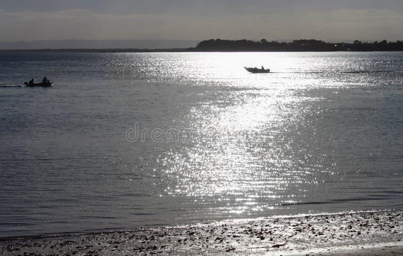 钓鱼在黄昏-旅行在与bokeh轻溢出的相反方向的两条小船横跨从做w的月亮的水 免版税库存照片