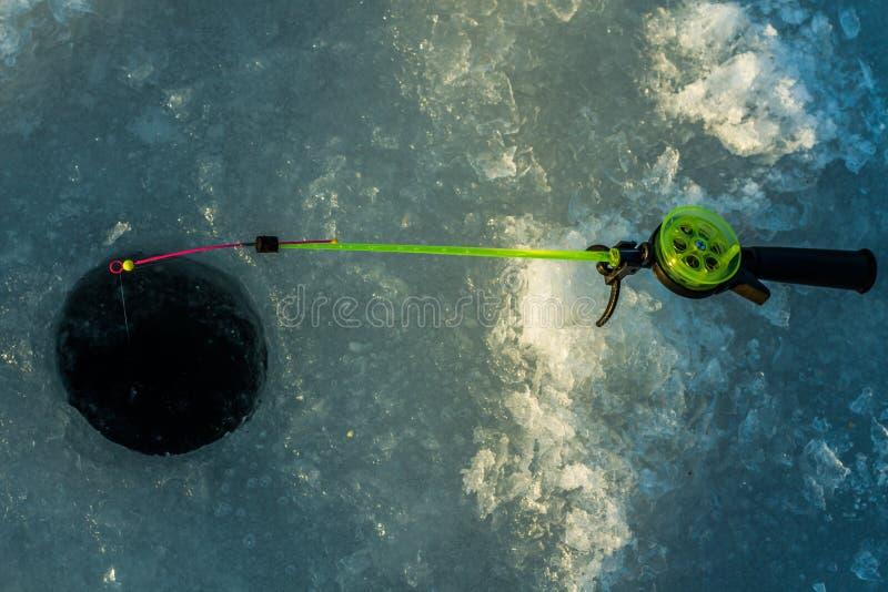钓鱼孔和钓鱼竿的冬天 免版税库存照片