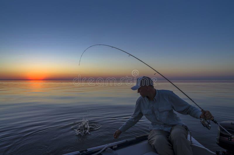 钓鱼早晨 小船抓住鱼的渔夫 免版税库存照片