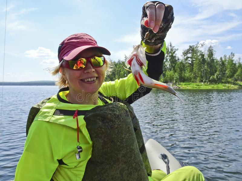 钓鱼是伟大的抓住 被抓的鱼在一位愉快的渔夫的手上 库存图片