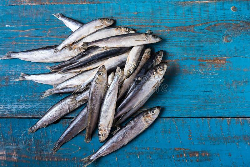 钓鱼模式 鲱鱼在老蓝色木背景钓鱼 库存图片