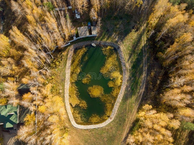 钓鱼的小人为水库池塘与金黄秋天foret树和村庄房子围拢的小船 r 图库摄影