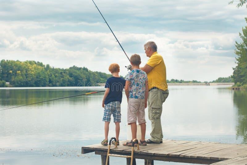 钓鱼的祖父教的孙子 图库摄影