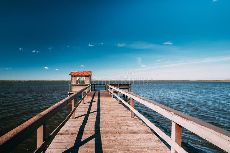 钓鱼的,小屋棚子和美丽的湖的木码头或者 图库摄影