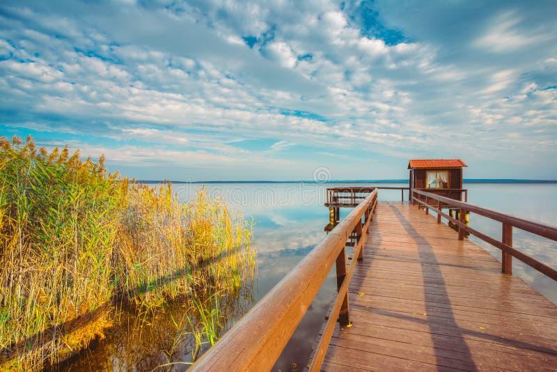 钓鱼的,小屋棚子和美丽的湖的老木码头 库存照片