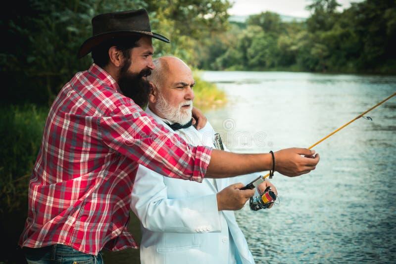 钓鱼竿和卷轴与斑鳟从小河 一起放松的父亲和的儿子 钓鱼在河的人在夏天期间 免版税库存图片