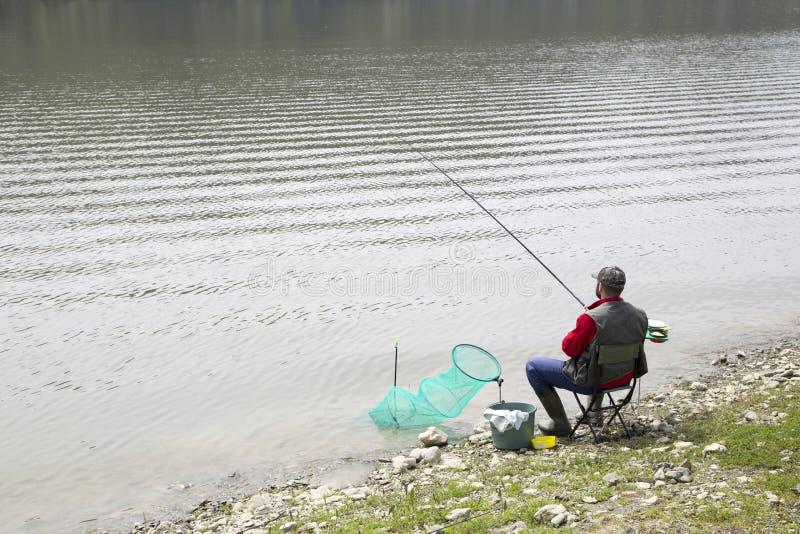 钓鱼者坐河海岸和耐心地等待的鱼采取诱饵 免版税库存照片