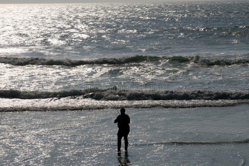 钓鱼者海滩现出了轮廓 库存图片