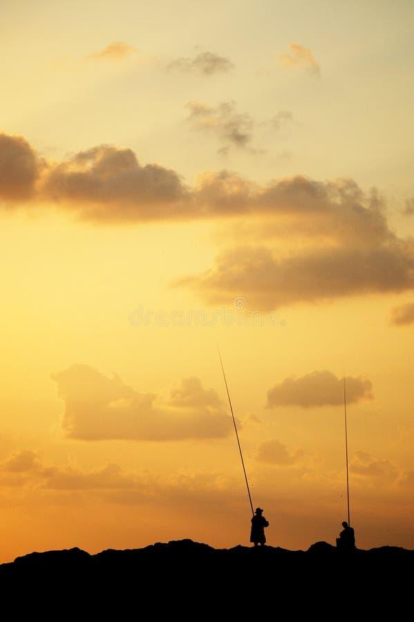 钓鱼者现出轮廓在日落 免版税图库摄影