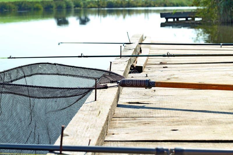钓鱼背景 捕鱼设备的减速火箭的被定调子的图片在木码头的 钓鱼在湖的平台 图库摄影