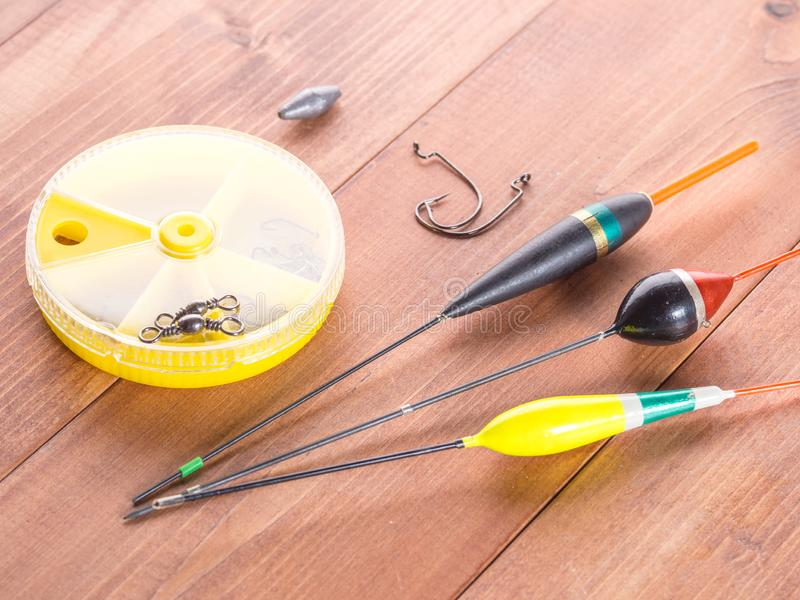 钓鱼辅助部件-浮游物,勾子,圆的黄色箱子,在木背景 图库摄影