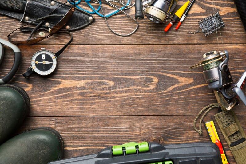 钓鱼题材 与胶靴的框架,鱼箱子,卷轴,钓鱼在木的浮体、指南针、饲养者、刀子和鱼串 库存照片