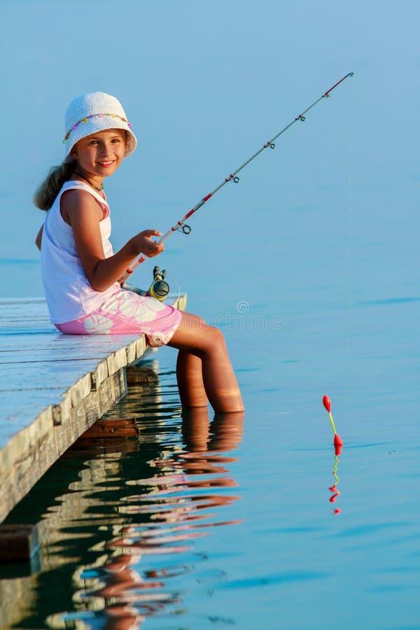钓鱼-在码头的可爱的女孩渔 免版税图库摄影