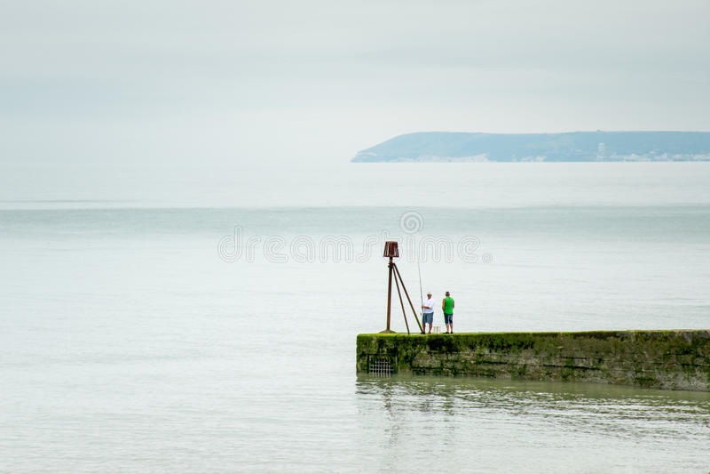 钓鱼groyne的人在风平浪静 库存图片
