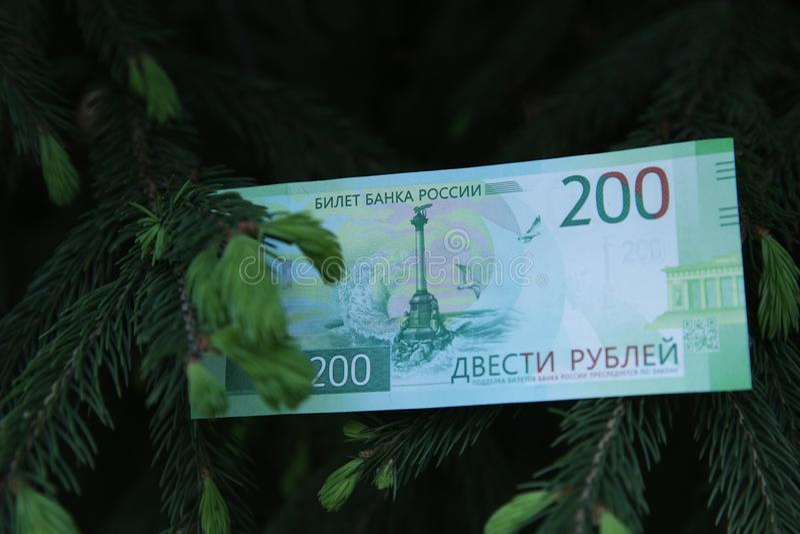 钞票二百俄罗斯卢布 在黑背景的现金纸私房钱与圣诞树分支 库存图片