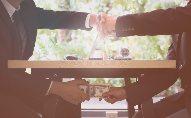 钞票概念毁坏美元信包查出的白色 关闭握手和收到美元金钱的两商人 贿款金钱 库存图片