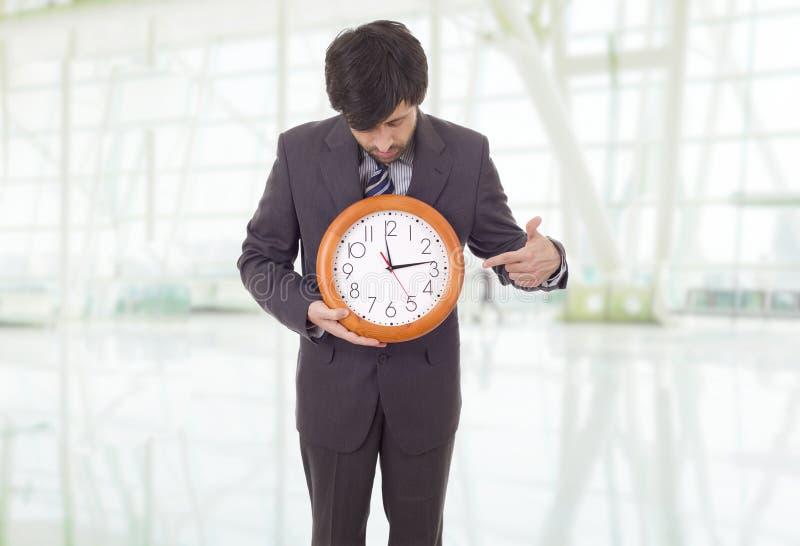 钟。在办公室有钟表的商人 库存照片