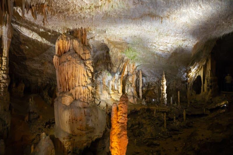 钟乳石和石笋在一个地下洞穴-波斯托伊纳洞,斯洛文尼亚看法  免版税库存图片